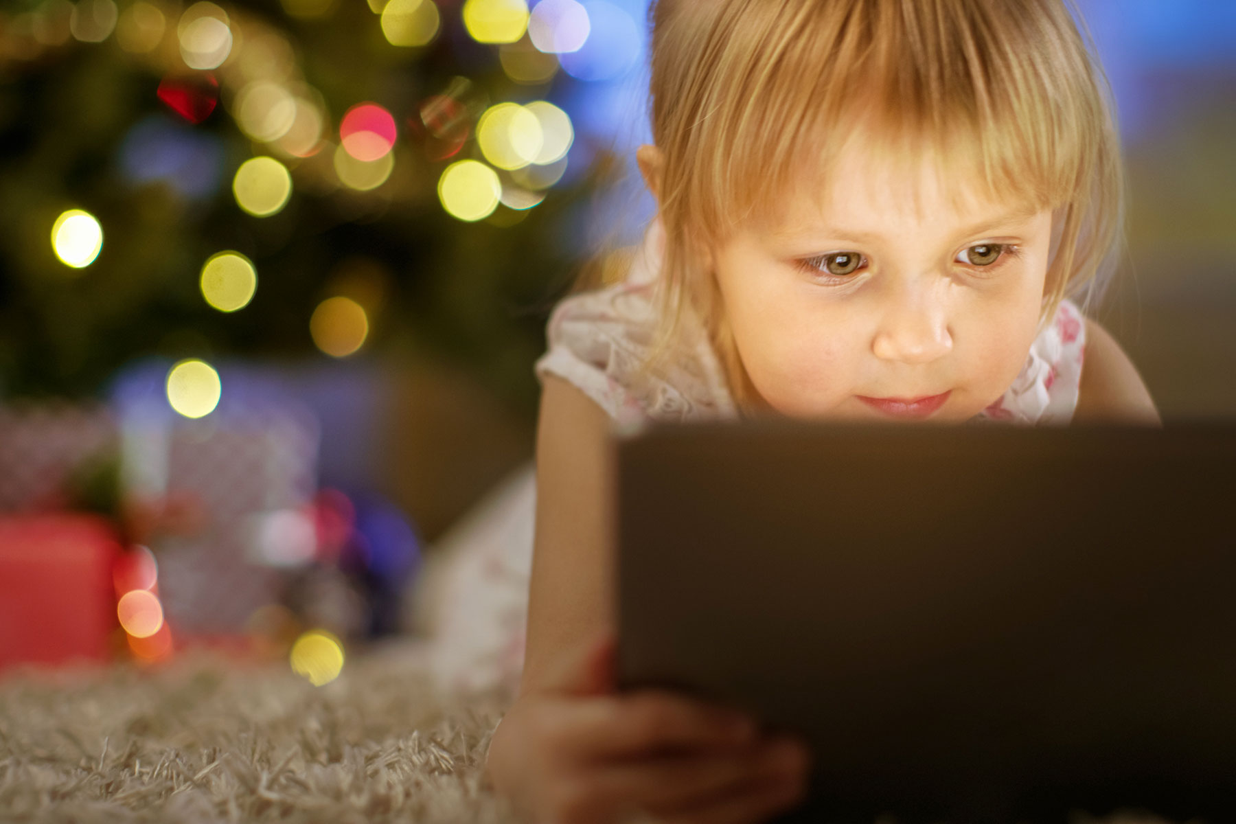 girl using tablet on clean carpeting holiday tree in background